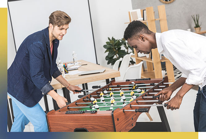 Two happy, young men playing foosball